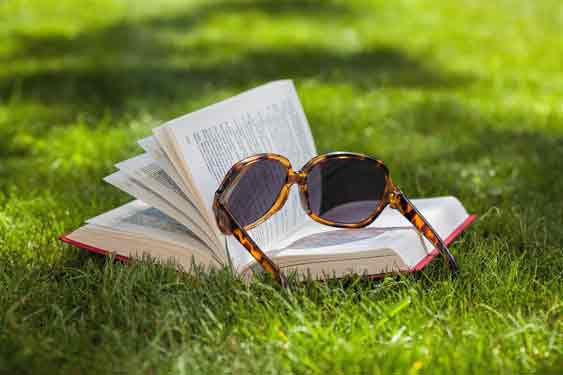 Book on grass with sunglasses